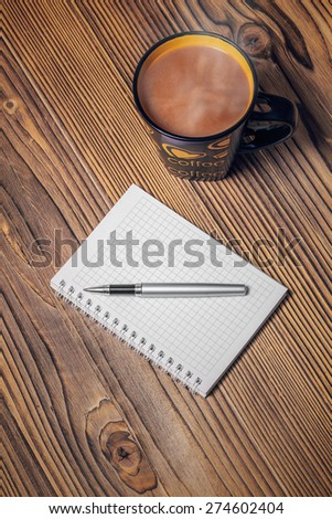 notepaper, coffee cup and pen on wood table - stock photo