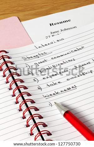 Notes for job interview, thinking of strengths and weaknesses, with resume in background. - stock photo