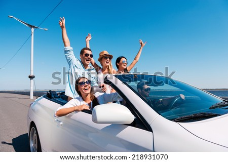 Nothing but friends and road ahead. Group of young happy people enjoying road trip in their white convertible and raising their arms up - stock photo