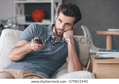 Nothing interesting to watch. Handsome young man holding remote control and looking bored while watching TV on the couch at home - stock photo