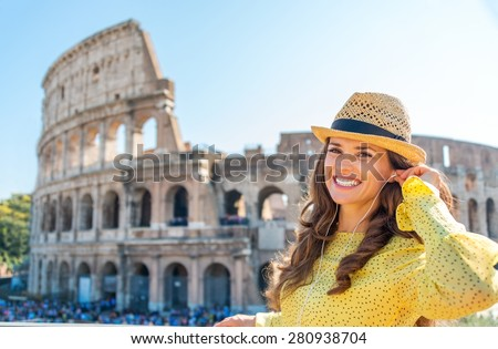 Nothing like listening to some tunes while being a tourist. A happy, smiling woman stands near the Colosseum, readjusting her earbuds. - stock photo