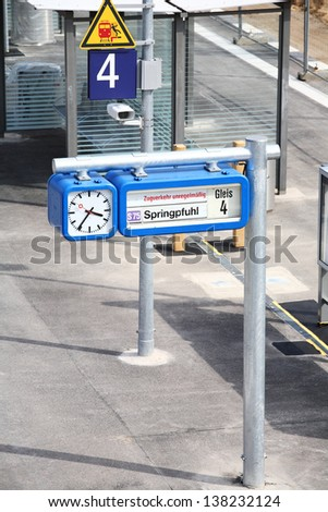 Notice board at a public railway station with a clock - stock photo
