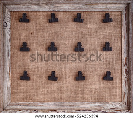 Notice board with hessian backing and twelve clips for holding notes, framed in a distressed wood