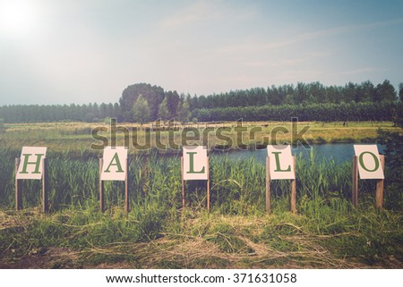 Notice boards in pasture spelling the dutch word for hello, instagram effect - stock photo