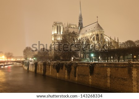 Notre Dame cathedral and Seine river in Paris by night - stock photo