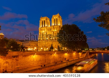 Notre Dame  cathedral facade and Seine embankment at blue night, Paris, France - stock photo