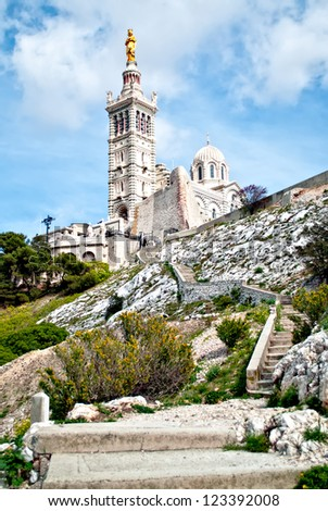 Notre-Dame de la Garde (literally Our Lady of the Guard), is a basilica in Marseille, France. This ornate Neo-Byzantine church is situated at the highest natural point in Marseille. - stock photo