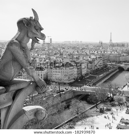 Notre Dame of Paris: Famous Chimera (gargoyle) overlooking the Eiffel Tower at a summer day - stock photo
