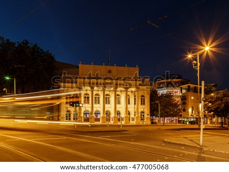 NOTTINGHAM, ENGLAND - AUGUST 30: Wide view of the Theatre Royal. Lights of a 'NET' tram are caught as traffic trails. In Nottingham, England. On 30th August 2016.