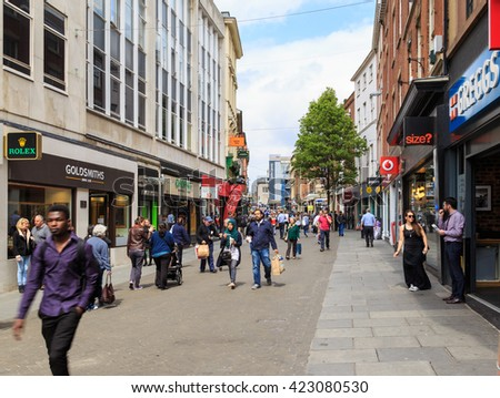 NOTTINGHAM, ENGLAND - MAY 17: Various people walking by the shops on Nottingham's busy Clumber Street. Various major retail stores visible. In Nottingham, England. On 17th May 2016. - stock photo