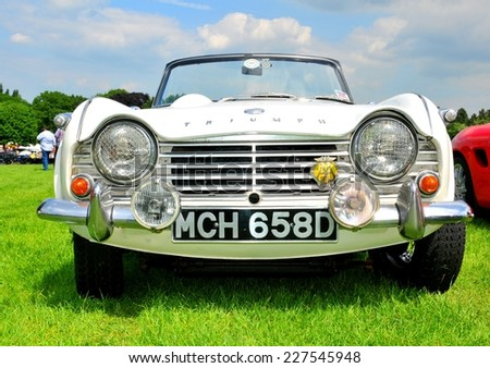 NOTTINGHAM, UK. JUNE 1, 2014: Frontal view of a white Triumph vintage car for sale in Nottingham, England. - stock photo