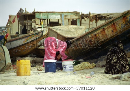 NOUAKCHOTT, MAURITANIA - JAN 5: Local woman cleans fish at the beach at January 5, 2006 in Nouakchott, Mauritania. Fresh fish is sold daily on the beach. - stock photo