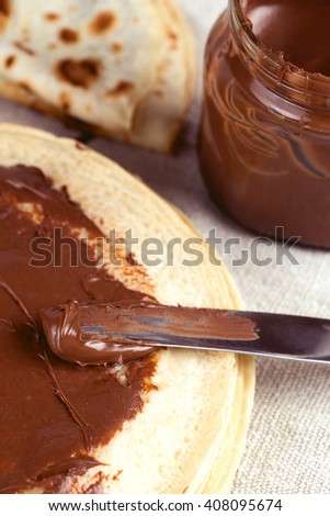 Nourishing and tasty breakfast crepes with nutella hazelnut chocolate spread. Knife spreading nutella over pancake. Shallow depth of field - stock photo