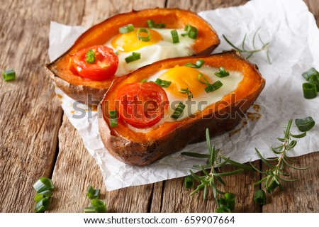 Nourishing food: stuffed sweet potato with fried egg and tomato close-up on the table. horizontal