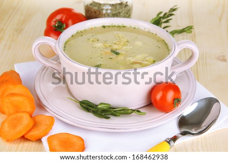 Nourishing soup in pink pan with ingredients on wooden table close-up