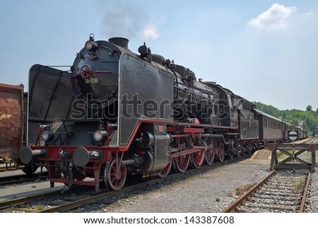 NOVA GORICA - JUNE 15: Classic German steam train model 06-018 pulling passenger carriages on JUNE 15, 2013 in Nova Gorica, Slovenia. - stock photo