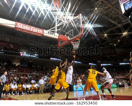 NOVEMBER 11 - PHILADELPHIA: Temple Owls forward Mark Williams (10) puts up a contested shot in the lane during the NCAA basketball game against Kent State November 11, 2013 in Philadelphia  - stock photo