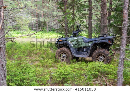 NOVGOROD REGION, RUSSIA - JULY 9, 2015: The modern quad bike parked at the forest in summer day - stock photo