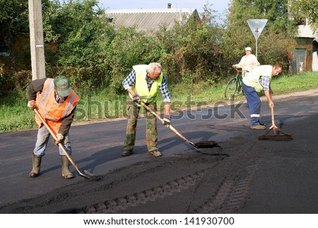 NOVGOROD REGION, RUSSIA - SEPTEMBER 7: Unknown road builders level asphalt mixture for repair of asphalt covering road in the city of Malaya Vishera, Novgorod region, Russia. September 7, 2011. - stock photo