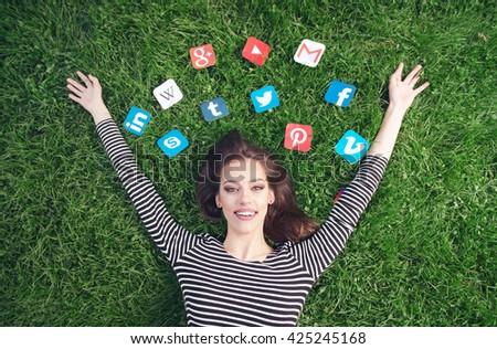 NOVI SAD, SERBIA - MAY 17, 2016: Young woman laying on the grass with Facebook, g mail, Instagram, Wikipedia, YouTube and other application icons. Editorial Use Only - stock photo