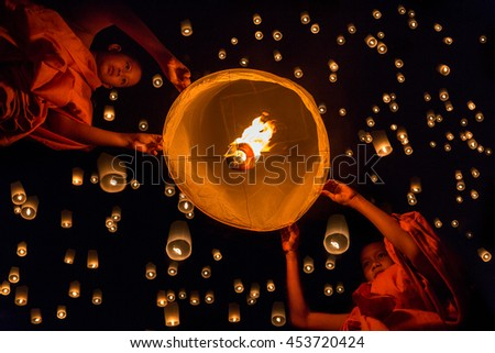 Novice monk lights floating lanterns made of paper in Loi Krathong or Loy Krathong day.
