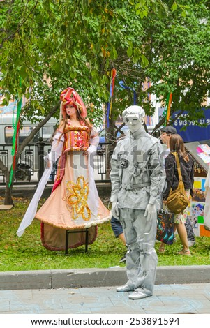 Novosibirsk, Russia - August 17, 2014: Unidentified busking mimes perform at central park in Novosibirsk. Living statues are the entertainment for the tourists. - stock photo
