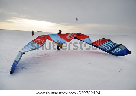 Novosibirsk, Russia, desember 15, 2016: Kite surfer ride on snowboard. Snowkiting in the snow on frozen sea. Novosibirsk, Russia