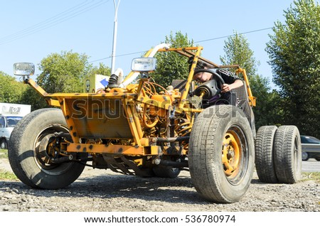 "Novosibirsk, Russia - June 20, 2016: Unknown brunette girl in costume ""Adidas"" climbs behind the wheel of a small racing car off-road buggy in Novosibirsk on 20 June 2016."