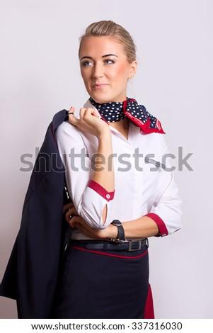 NOVOSIBIRSK, RUSSIA - NOVEMBER 02, 2015: Transaero Crew member (flight attendant) Dressed In Uniform On Gray Background. Transaero - largest private Russian airline has terminated operations Oct 2015 - stock photo