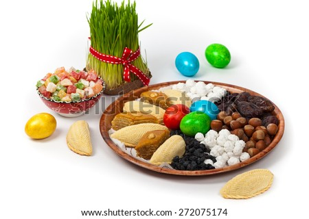 Novruz in Azerbaijan. Colored eggs for easter and traditional sweets on white background. Selective focus. - stock photo