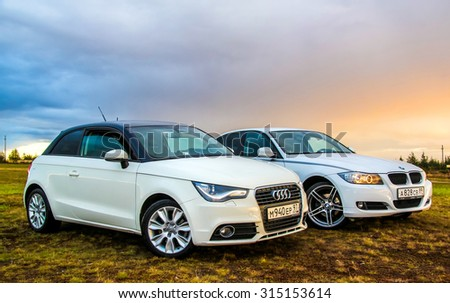NOVYY URENGOY, RUSSIA - AUGUST 21, 2015: Motor cars Audi A1 and BMW E90 318i at the countryside. - stock photo