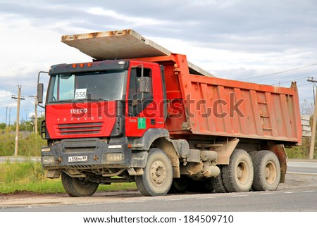 NOVYY URENGOY, RUSSIA - AUGUST 5, 2012: Red Iveco Trakker dump truck at the city street.