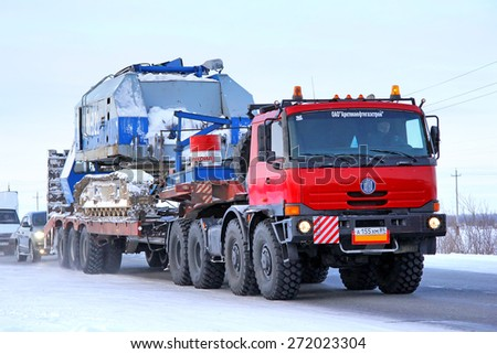 NOVYY URENGOY, RUSSIA - FEBRUARY 14, 2015: Heavy semi-trailer truck Tatra TerrNo1 carries a heavy industrial machinery at the interurban road. - stock photo