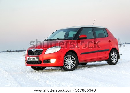 NOVYY URENGOY, RUSSIA - JANUARY 30, 2016: Red bright compact car Skoda Fabia Sport Edition is parked in the snow covered tundra at the background of the sunset. - stock photo