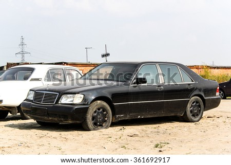 NOVYY URENGOY, RUSSIA - JULY 27, 2013: Abandoned motor car Mercedes-Benz W140 S-class at the city street.