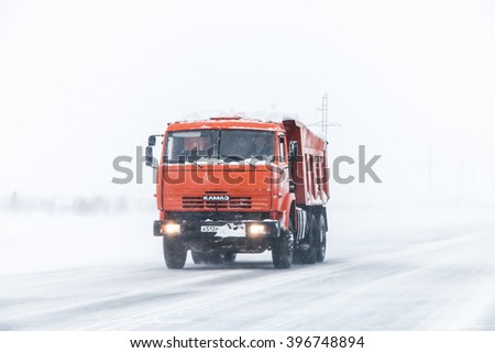 NOVYY URENGOY, RUSSIA - MARCH 20, 2016: Dump truck Kamaz 65115 at the interurban freeway during a heavy northern blizzard.