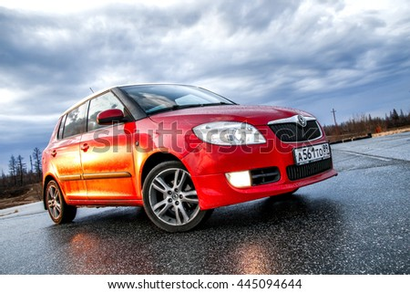 NOVYY URENGOY, RUSSIA - MAY 26, 2016: Bright red compact hatchback car Skoda Fabia SE in the town street during a rain. - stock photo