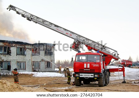 NOVYY URENGOY, RUSSIA - MAY 9, 2015: Modern fire ladder KAMAZ 43114 AL-30 near the burning old wooden residential house. - stock photo