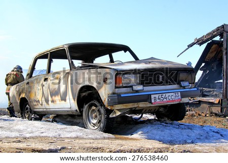NOVYY URENGOY, RUSSIA - MAY 10, 2015: Old car near the wooden residential house after a heavy fire. - stock photo