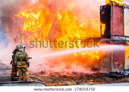 NOVYY URENGOY, RUSSIA - MAY 14, 2015: Old wooden residential house burns with black smoke and heavy flames.