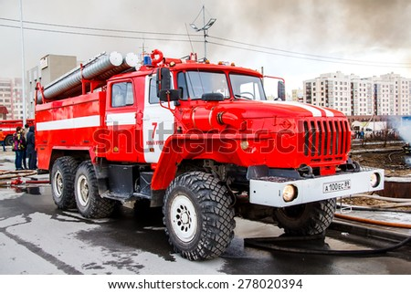 NOVYY URENGOY, RUSSIA - MAY 14, 2015: Red firetruck Ural 5557 takes part in the extinguishing of a fire in an old wooden house. - stock photo