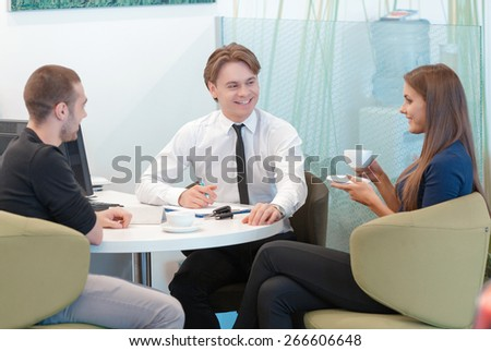 Now her dream has come true. Young handsome sales consultant communicates with customers sitting by the table and drinking coffee  - stock photo