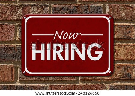 Now Hiring Sign,  A red sign with the word Now Hiring with an arrow on a brick wall