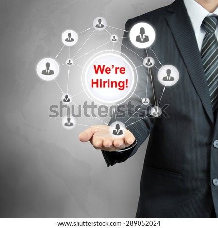 Now Hiring sign on businessman hand, HR and recruitment concepts - stock photo