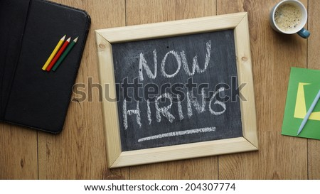 Now hiring written on a chalkboard at the office - stock photo