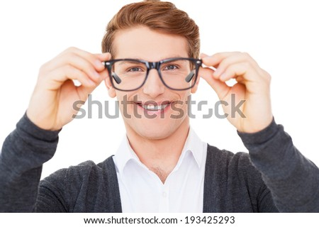 Now I can see you well. Handsome young man holding glasses and looking through them while standing isolated on white