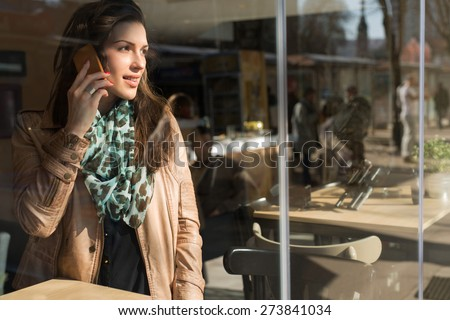 Nowhere without a phone. Trendy and beautiful young woman talking on a smart phone, keeping in touch with her friends. - stock photo