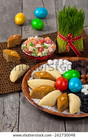 Nowruz holiday in Azerbaijan. Colored eggs for easter and traditional sweets. Selective focus. - stock photo