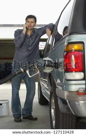 Nozzle inserted into car tank with man on a call in the background - stock photo