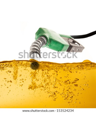 Nozzle pumping gasoline in a tank - stock photo
